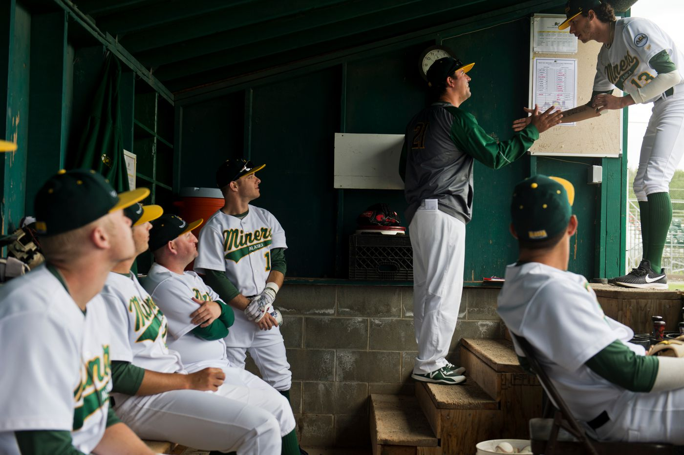 Miners coach Tyler LeBrun slaps hands with pitcher Randy Abshier, right. (Marc Lester / ADN)
