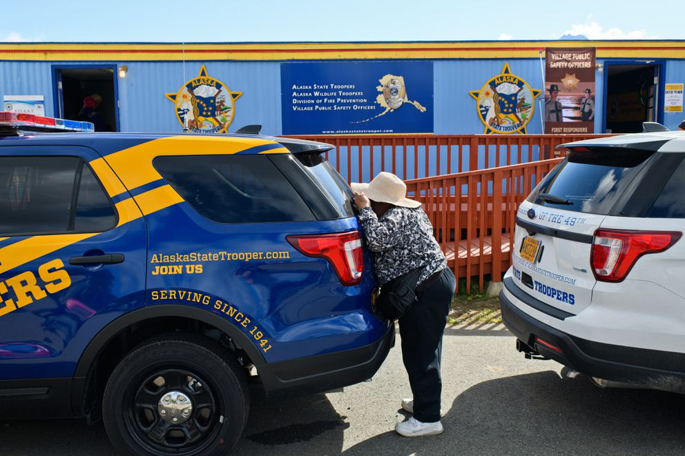 Maria York, of Anchorage, takes a peek inside an Alaska State Trooper recruitment vehicle at the Alaska State Fair. Trooper vehicles on display at the Alaska State Fair show proposed design changes on August 28, 2018. (Marc Lester / ADN)