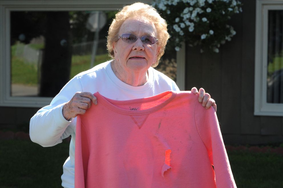 Donna Rodgers holds the sweatshirt she was wearing when a cow moose attacked her ripping a hole with her hoof. 'She really wanted to get me, ' Rodgers said at her Anchorage home on Thursday, June 4, 2020. (Bill Roth / ADN)