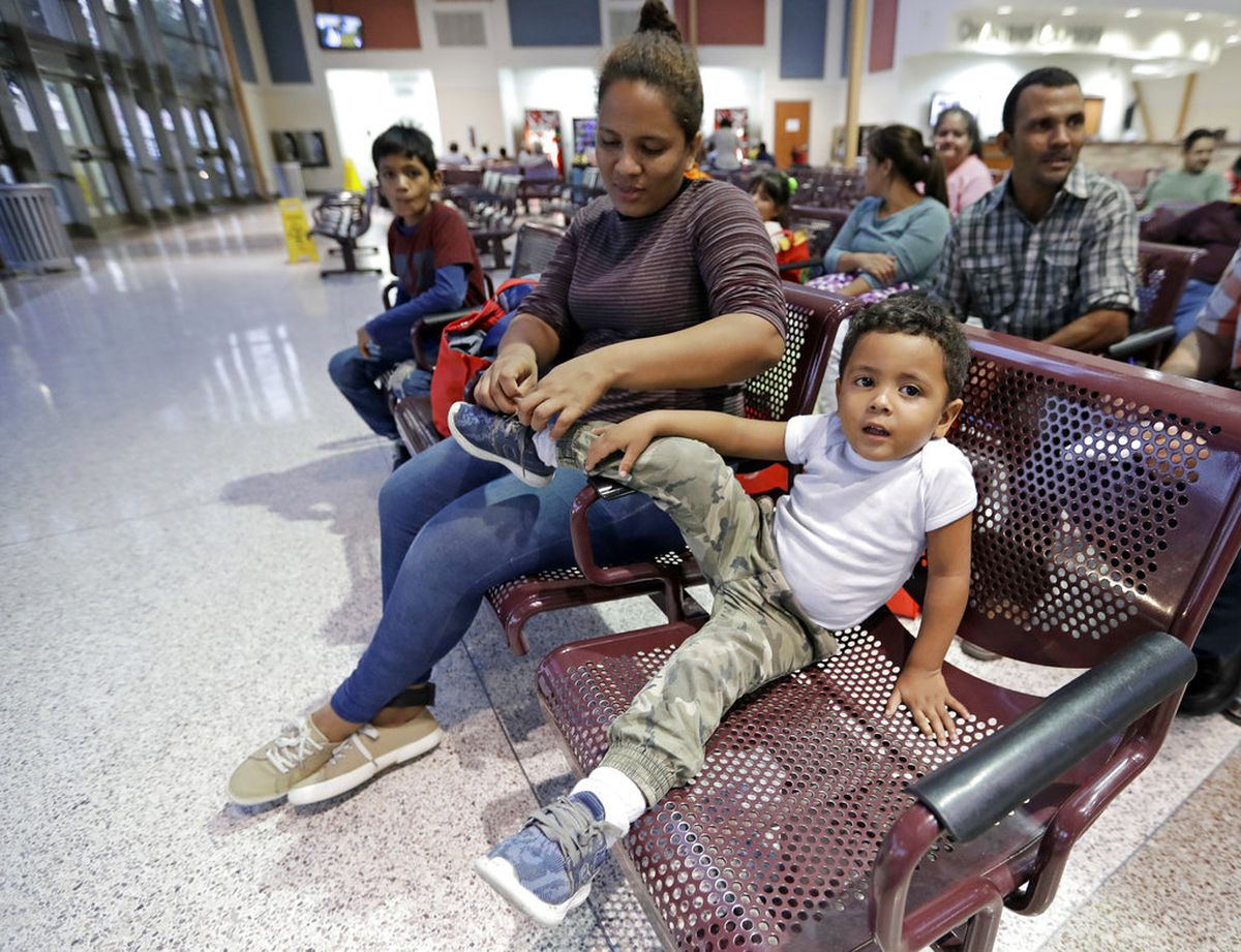Immigrant Patricia Lozano, from Honduras, ties her son's, Diego, shoe inside the bus station Saturday, June 23, 2018, in McAllen, Texas. The family was processed and released by U.S. Customs and Border Protection. (AP Photo/David J. Phillip)