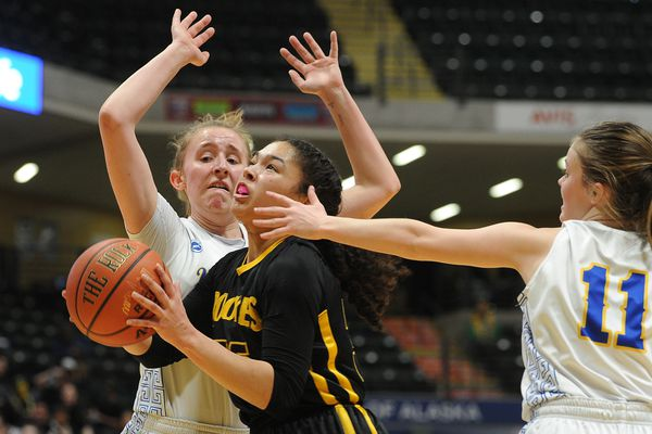 King Cove's Jalaya Durate, center, drives to the basket as Tri-Valley's Rachel Cockman, left, and Jazmyn Byfuglien defend in the Class 1A girls state basketball championship game at the Alaska Airlines Center on Saturday, March 16, 2019. (Photo by Bob Hallinen)