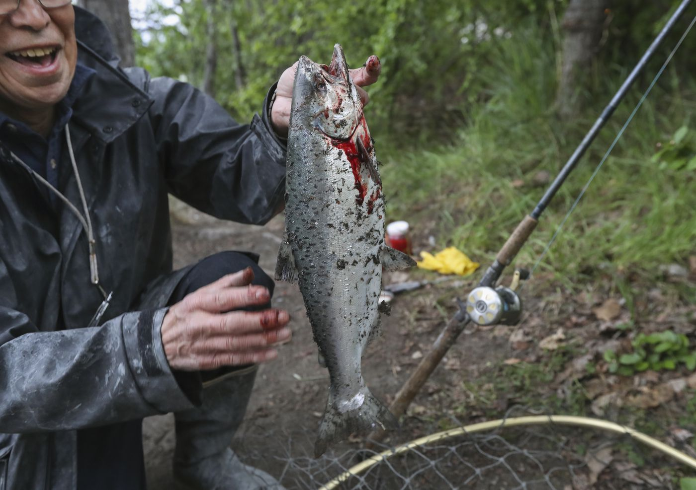 Harold Richards removes dirt and pebbles from a salmon his caught in Ship Creek in Anchorage on Wednesday, June 9, 2021. (Emily Mesner / ADN)