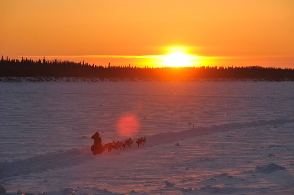 Mark Selland heads out on the Yukon River at sunset Wednesday, leaving the village of Tanana behind. (Bob Hallinen / Alaska Dispatch News)
