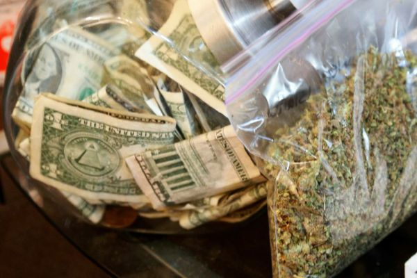 FILE PHOTO: A bag of marijuana being prepared for sale sits next to a money jar at BotanaCare in Northglenn, Colorado, U.S., December 31, 2013. REUTERS/Rick Wilking/File Photo