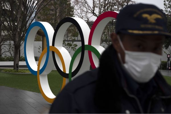 A security guard walks past the Olympic rings near the New National Stadium in Tokyo, Monday, March 23, 2020. The IOC will take up to four weeks to consider postponing the Tokyo Olympics amid mounting criticism of its handling of the coronavirus crisis that now includes a call for delay from the leader of track and field, the biggest sport at the games. (AP Photo/Jae C. Hong)