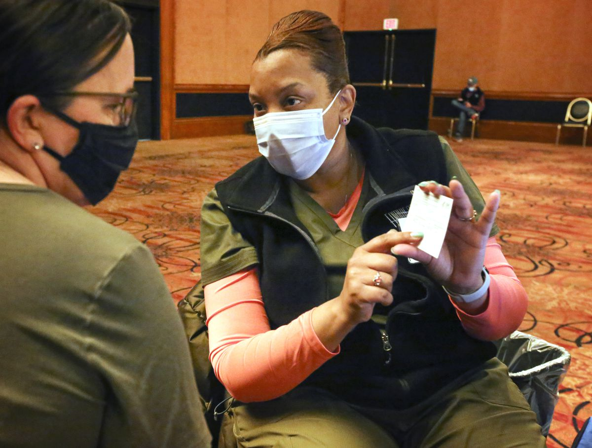Registered nurse Shawnece Stovall explains the vaccination card to Carmen Jones before she administers Jones' first dose of the Pfizer-BioNTech COVID-19 vaccine at a clinic set up in the Discovery Ballroom at Hotel Captain Cook in downtown Anchorage on Wednesday, March 24, 2021. Appointments for the COVID-19 vaccine can be found at www.anchoragecovidvaccine.org or by contacting the state call center at 907-646-3322. (Emily Mesner / ADN)
