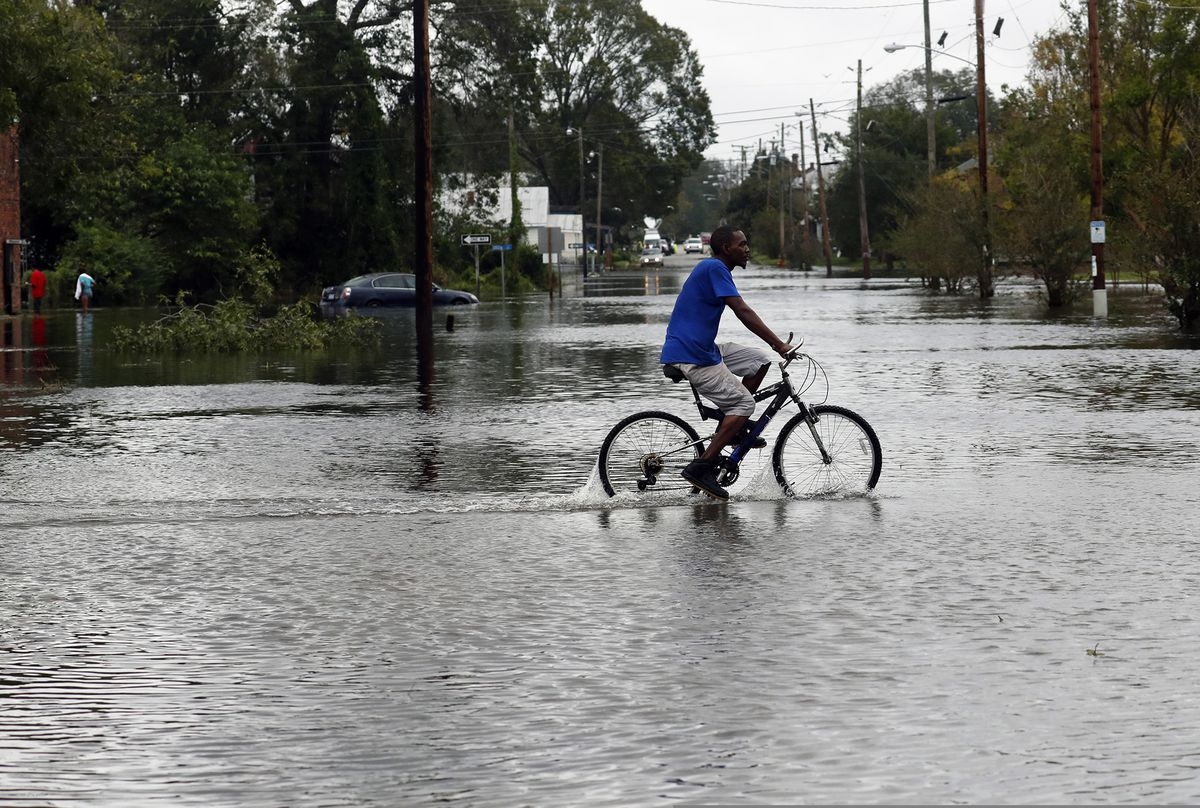 A man rides a bicycle on a street covered by floodwaters caused by the tropical storm Florence in New Bern, N.C., on Saturday Sept. 15, 2018. (AP Photo/Chris Seward)