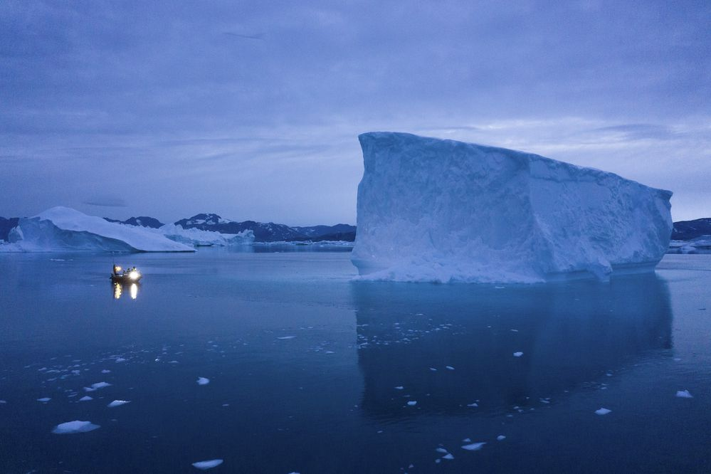 FILE - In this Aug. 15, 2019, file photo, a boat navigates at night next to large icebergs in eastern Greenland. Rising temperatures and diminished snow and ice cover in the Arctic are imperiling ecosystems, fisheries and local cultures, according to a report issued Tuesday, Dec. 10 by the National Oceanic and Atmospheric Administration. (AP Photo/Felipe Dana, File)