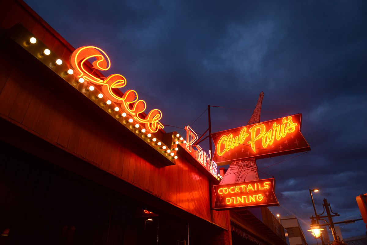 The neon sign on the Club Paris restaurant glows against the evening sky along Fifth Avenue in downtown Anchorage. (Bob Hallinen / ADN)