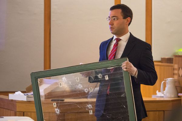 Assistant district attorney James Klugman holds up Precious Alex's bullet-hole ridden bedroom window during closing arguments in the jury trial of Lammar Burney and Jamal Townsend on Thursday, October 5, 2017. Alex was shot and killed on April 1, 2014, while sleeping in bed at her home in Mountain View. She was pronounced dead at a local hospital after being shot twice, once in the leg and once in the abdomen. (Loren Holmes / Alaska Dispatch News)