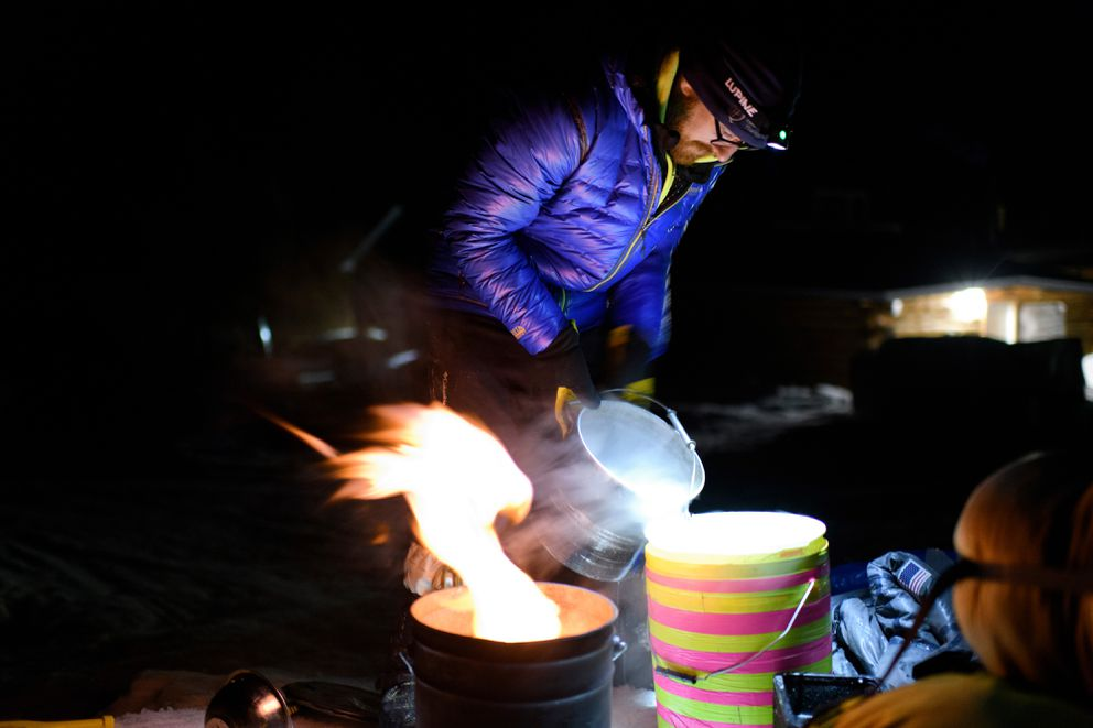 Wade Marrs pours hot water in Shageluk during the Iditarod on March 8, 2019. (Marc Lester / ADN)