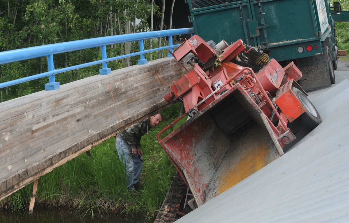 BILL ROTH / Anchorage Daily News Workers prepare to remove a wood chipper after a bridge near Westchester Lagoon collapsed when a Gage Tree Service truck was driving north on the Tony Knowles Coastal Trail to a job site on Monday, June 16, 2014.