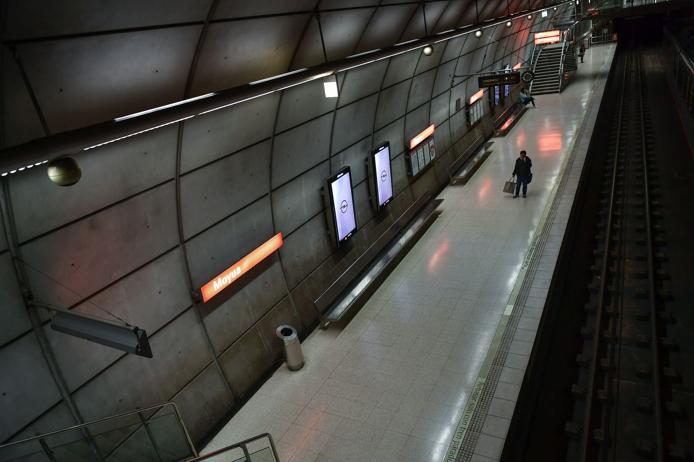 Passengers wait in an empty subway station, in Bilbao, northern Spain, Saturday, March 14, 2020. Spain's prime minister has announced a two-week state of emergency from Saturday in a bid to contain the new coronavirus outbreak. (AP Photo/Alvaro Barrientos)
