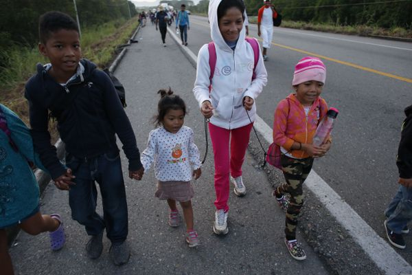 Migrant Fany Lizeth Cruz walks with cords attaching her wrists to those of her daughter, right, and another little girl, as her son walks alongside, outside Tapanatepec, Mexico, Monday, Oct. 29, 2018. Thousands of Central American migrants traveling together for safety resumed their journey after taking a rest day Sunday, while hundreds more migrants were pushing for entry to Mexico. (AP Photo/Rebecca Blackwell)