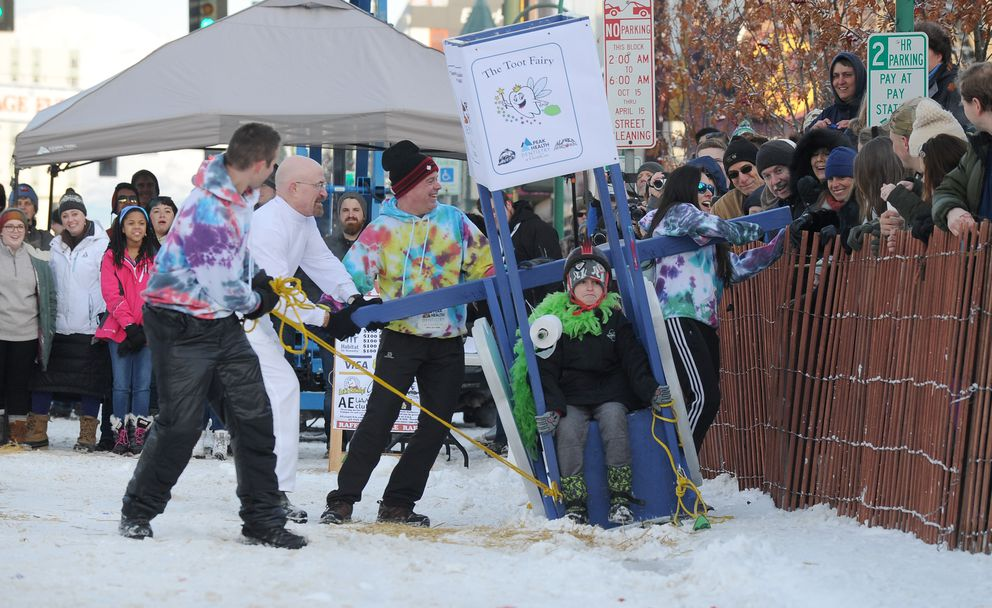 Ben Mishler, Tom Lannan, Mark Just and Valerie Stewart work to untangle their outhouse from the snow fence as rider Reed Douhith waits patiently during the Rondy Outhouse Races on Fourth Avenue in 2017. Peak Health Dentistry sponsored the Toot Fairy team. (Bob Hallinen / Alaska Dispatch News)