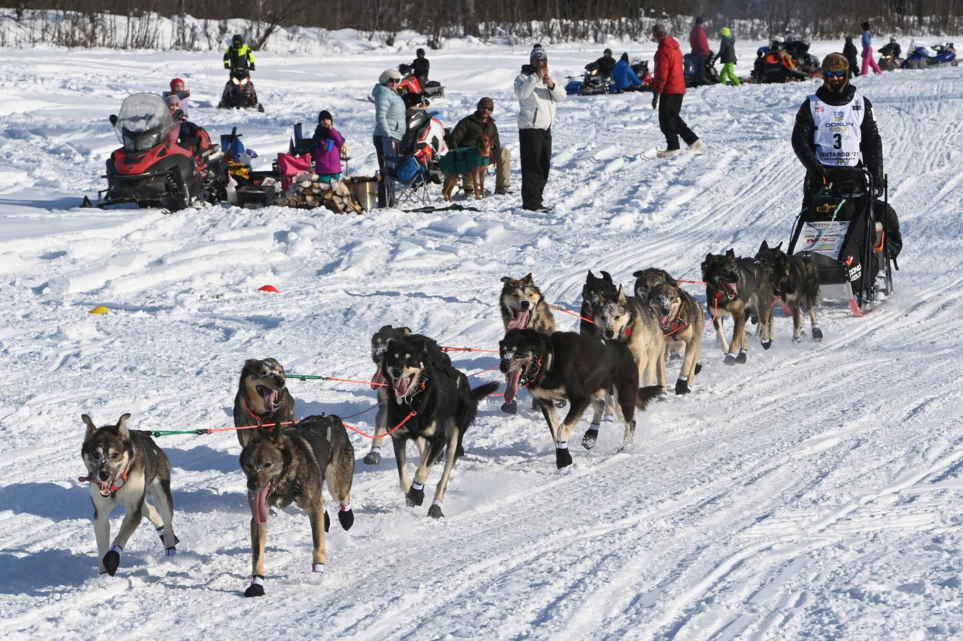 Iditarod champion Pete Kaiser drives his dog team past spectators on the Susitna River during the start of the Iditarod Trail Sled Dog Race in Willow on Sunday, March 7, 2021. (Bill Roth / ADN)