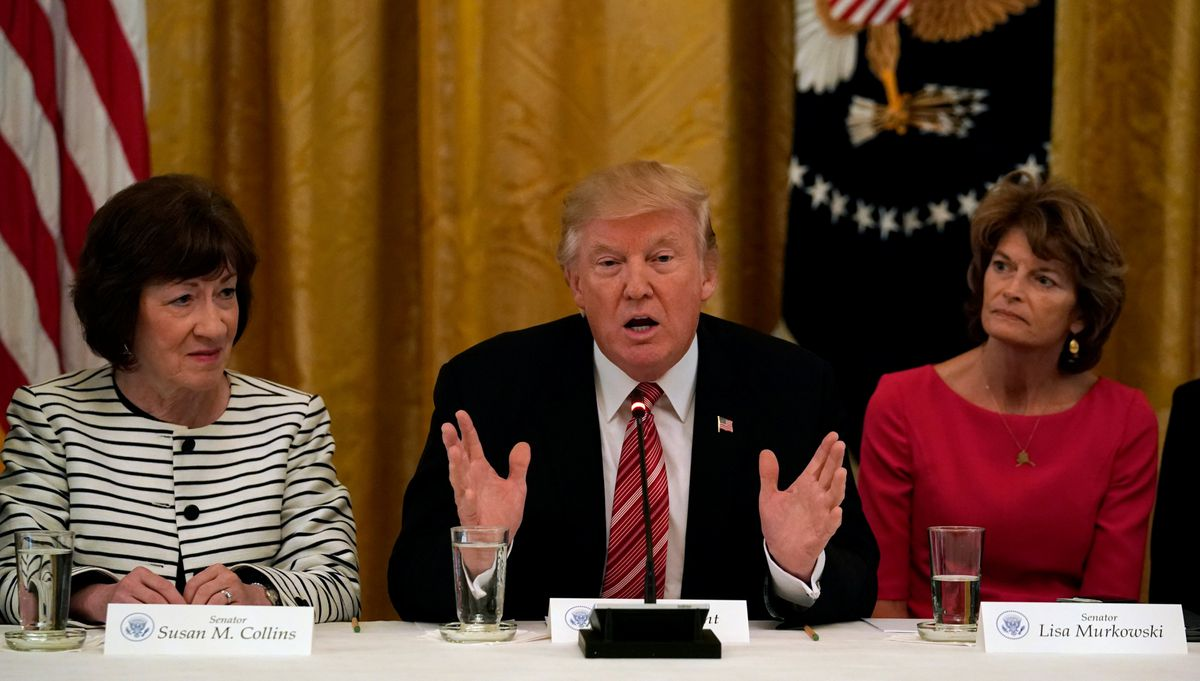President Donald Trump meets with Senate Republicans about health care in the East Room of the White House in WashingtononTuesday. Trump is flanked by Sens. Susan Collins, R-Maine, and Sen. Lisa Murkowski, R-Alaska. (Kevin Lamarque / Reuters)