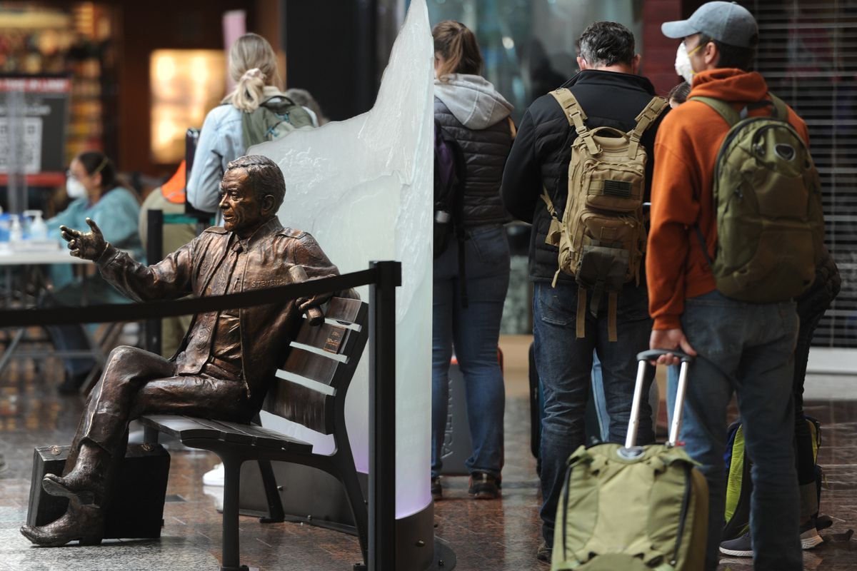 Air travelers entering Alaska wait in line for the screening station stand near a statue of the late Sen. Ted Stevens at Ted Stevens Anchorage International Airport on Monday, June 22, 2020. A health mandate requires passengers entering Alaska provide proof of a negative COVID-19 PCR test and proof of completed travel declaration. (Bill Roth / ADN)