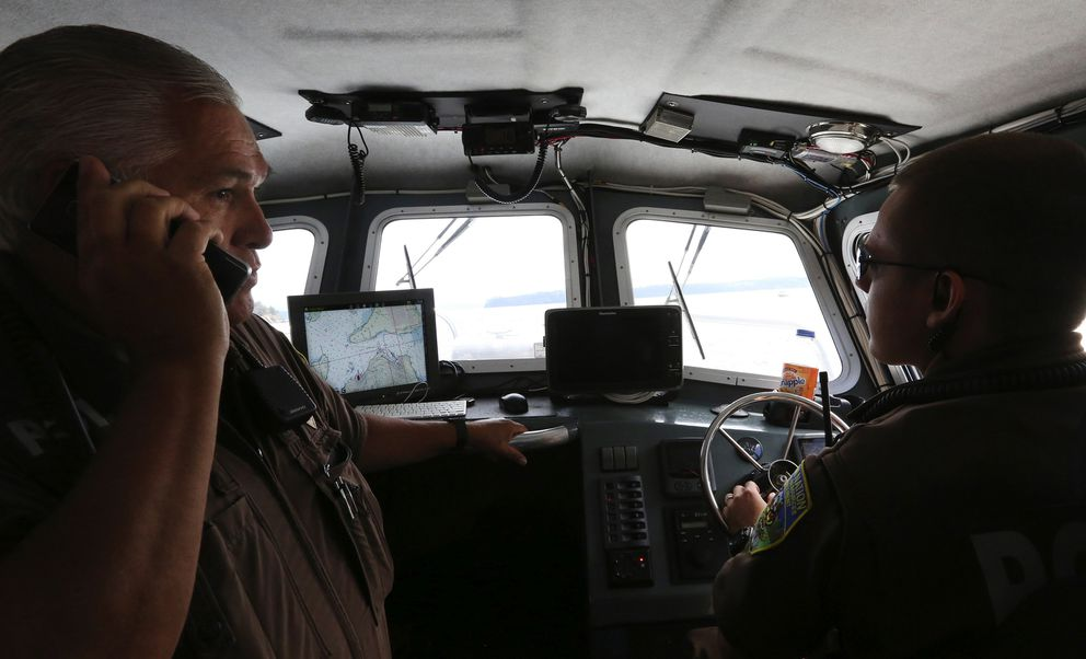 Lummi enforcement officers (Natural Resources) Sgt. Edward Conway, left, and Malcolm Owings, at the helm, cruise the waters off Cooke Aquaculture's destroyed Atlantic salmon fish pen off Cypress Island. (Alan Berner/Seattle Times/TNS)