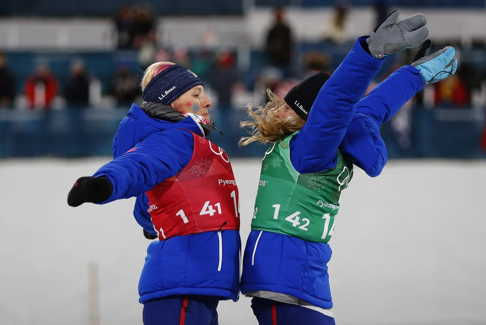 Kikkan Randall, left, and Jessica Diggins chest-bump on the podium. (REUTERS/Dominic Ebenbichler)