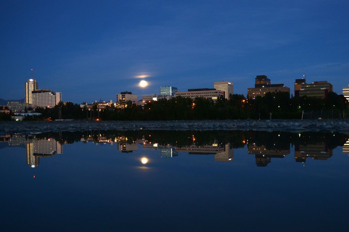 The Anchorage skyline is reflected in a puddle as the moon rises above the city in Anchorage, Alaska on Sunday, August 6, 2017. (Bob Hallinen / ADN)
