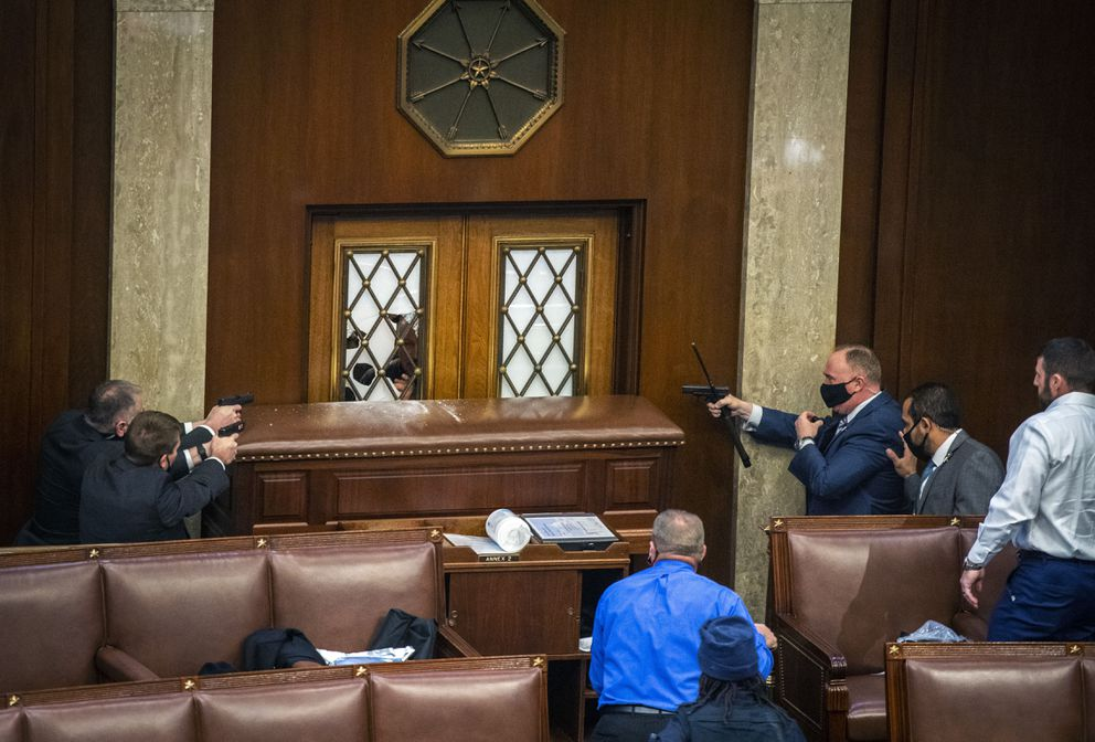 Security officers point weapons at a House chamber door as a mob of rioters storms the Capitol on Wednesday, Jan. 6, 2021. (Washington Post photo by Bill O'Leary)