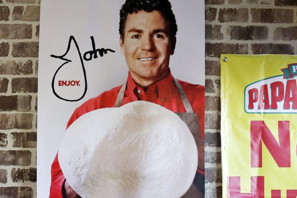 FILE- In this Dec. 21, 2017, file photo shows signs, including one featuring Papa John's founder John Schnatter, at a Papa John's pizza store in Quincy, Mass. Papa John's plans to pull Schnatter's image from marketing materials following use of racial slur. Schnatter apologized Wednesday, July 11, 2018, and said he would resign as chairman after Forbes reported that he used the slur during a media training session. Schnatter had stepped down as CEO last year after criticizing NFL protests. (AP Photo/Charles Krupa, File)