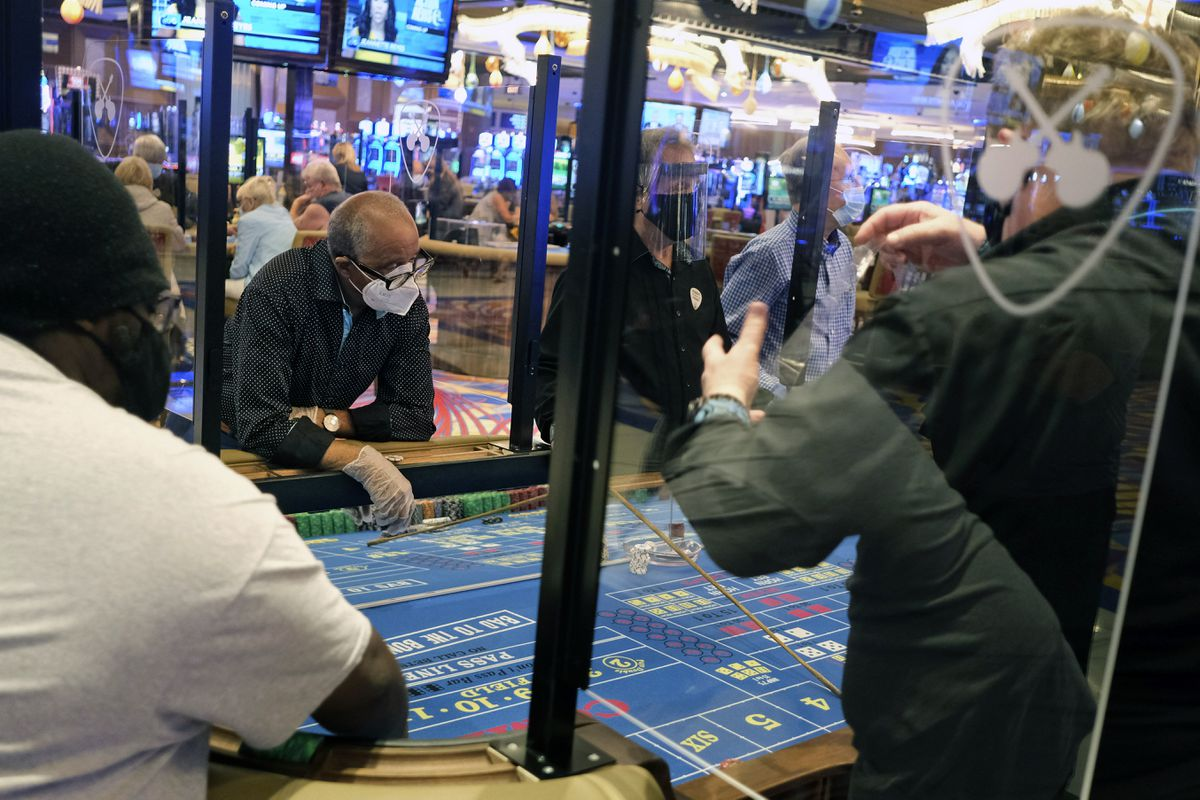 Partitions between players and face masks allow gamblers to enjoy craps at the Hard Rock Casino in Atlantic City, N.J., Thursday, July 2, 2020. Eager to hit the slot machines and table games after a 108-day absence, gamblers wore face masks and did without smoking and drinking Thursday as Atlantic City's casinos reopened amid the coronavirus pandemic that has drastically changed things both inside and outside the casino walls. (AP Photo/Seth Wenig)