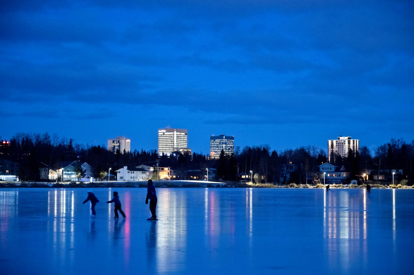 Lights of downtown Anchorage reflect on the frozen surface of Westchester Lagoon. (Marc Lester / ADN)