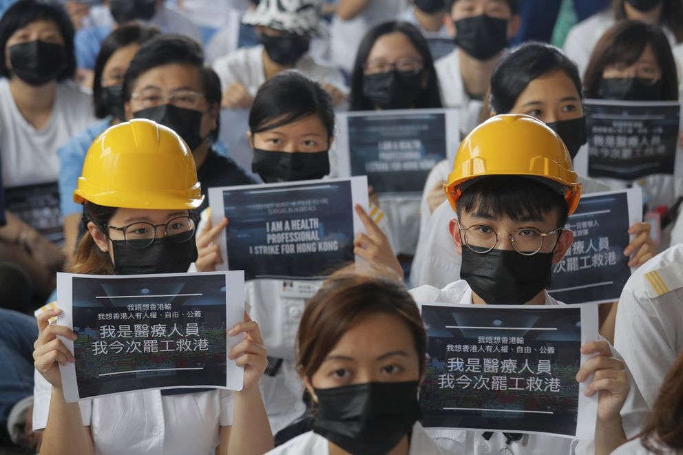 Medical staff take part in a protest against police brutality on the protesters, at a hospital in Hong Kong, Tuesday, Aug. 13, 2019. Demonstrators have in recent days focused on their demand for an independent inquiry into what they call the police's abuse of power and negligence. That followed reports and circulating video footage of violent arrests and injuries sustained by protesters. The signs read ' I'm a health professional, I strike for Hong Kong. ' (AP Photo/Kin Cheung)