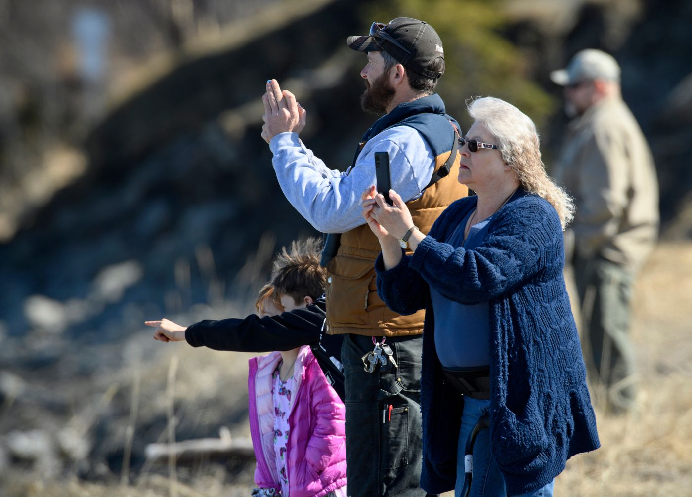People gather along the Kenai River near Bridge Access Road to catch a glimpse of beluga whales as they travel upriver on April 25, 2021. (Marc Lester / ADN)