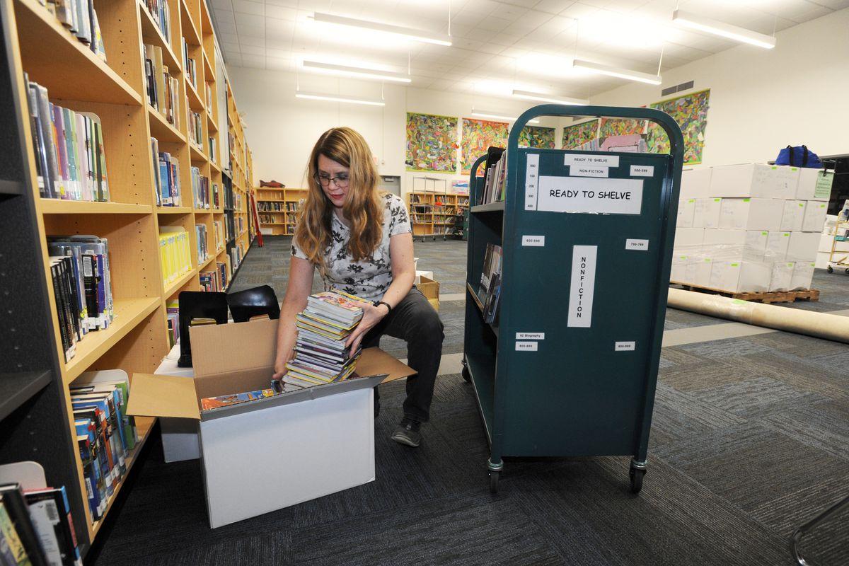 Librarian Laura Guest unpacks books as she re-stocks some shelves in her renovated library on Thursday, Jan. 5, 2017, at Turnagain Elementary School. (Erik Hill / Alaska Dispatch News)