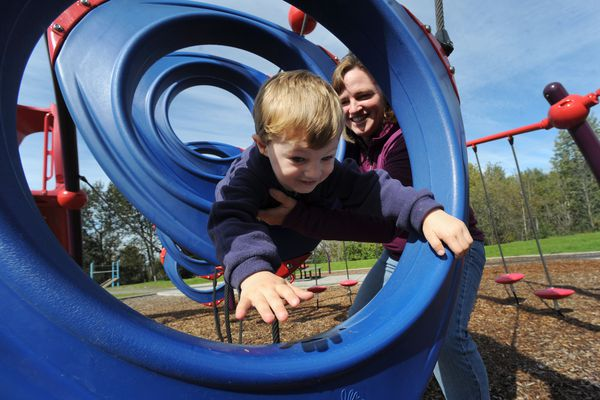 Colleen Carlson, author of the book 133 Anchorage Playgrounds, spots her 4-year-old son James as he climbs on playground equipment at Margaret Eagan Sullivan Park near Westchester Lagoon on Wednesday, Aug. 24, 2016. (Bill Roth / Alaska Dispatch News)