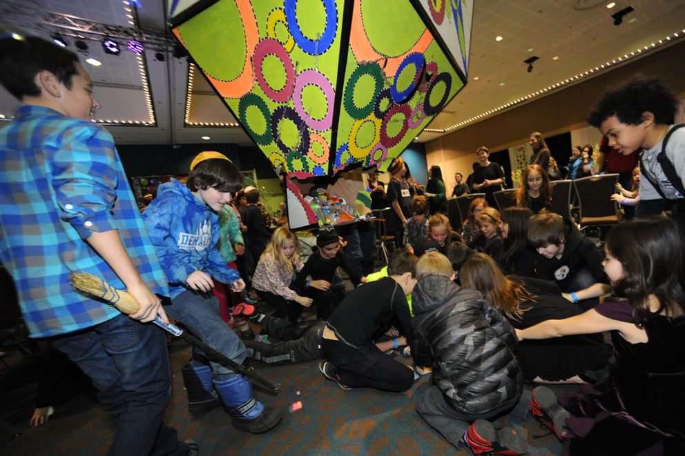 Jack Green, 14, left, watches children scramble after he broke a giant dreidel Piñata with a broom stick during Cirque De Chanukah held by the Alaska Jewish Campus & Lubavitch Jewish Center at the Egan Center in Anchorage on Sunday, Dec. 6, 2015. A ice menorah kindling ceremony was also held marking the first day of the Jewish holiday Chanukah which is observed for eight days and nights.(Bill Roth / ADN)