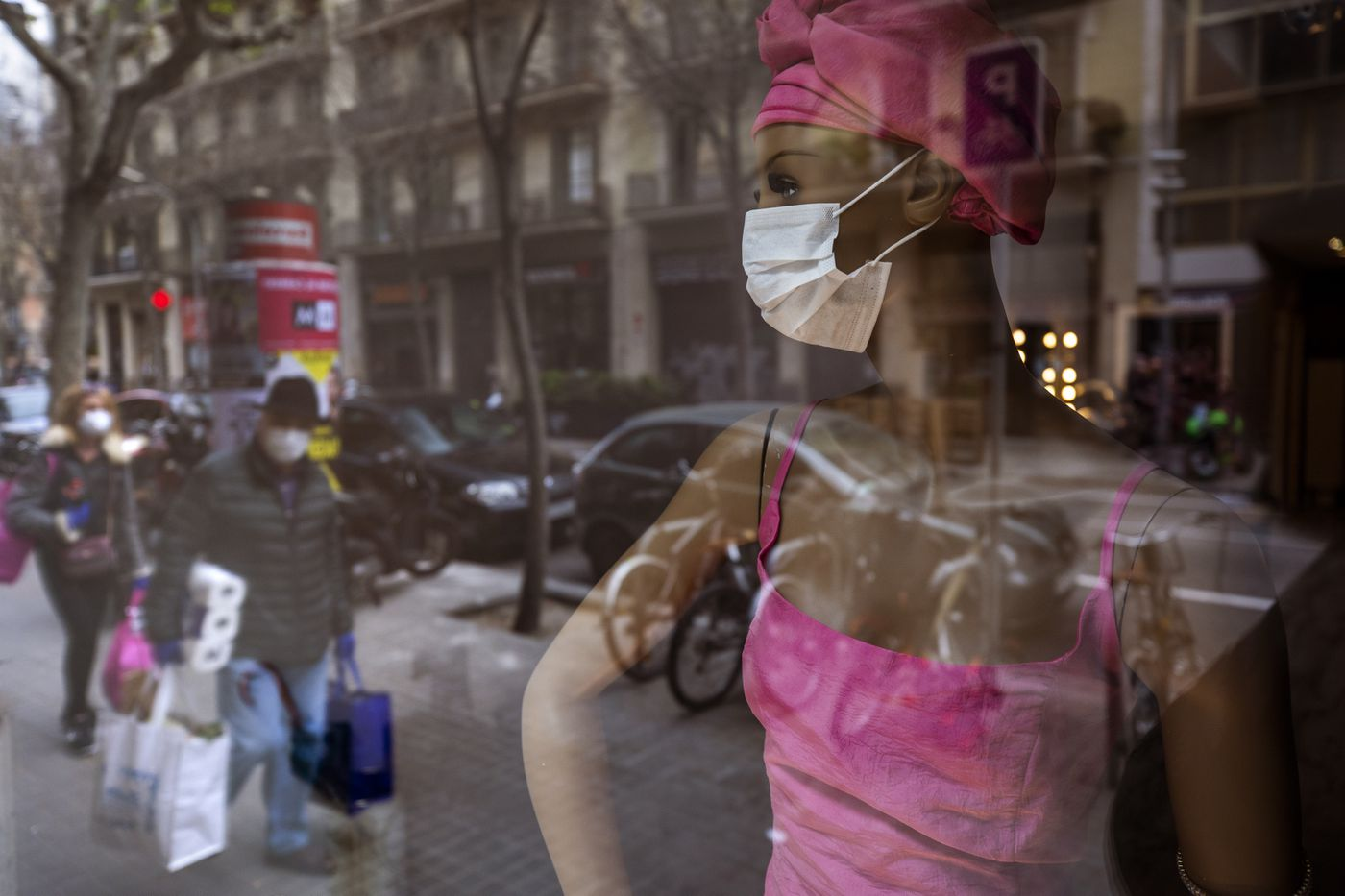 People wearing masks and carrying supplies walk past a mannequin wearing a mask in downtown Barcelona, Spain, Saturday, March 14, 2020. Spain's prime minister has announced a two-week state of emergency from Saturday in a bid to contain the new coronavirus outbreak. (AP Photo/Emilio Morenatti)