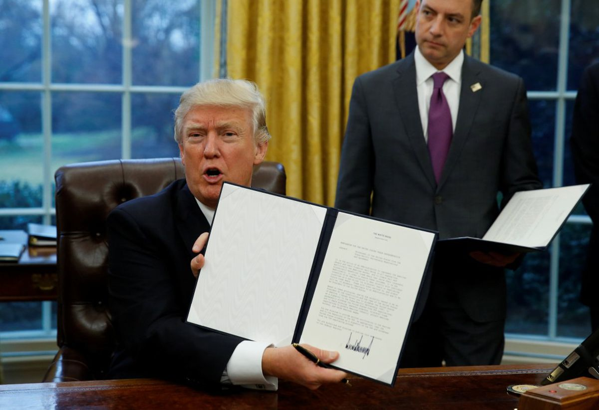 President Donald Trump holds up the executive order on withdrawal from the Trans Pacific Partnership after signing it as White House Chief of Staff Reince Priebus stands at his side in the Oval Office of the White House in Washington January 23, 2017. REUTERS/Kevin Lamarque