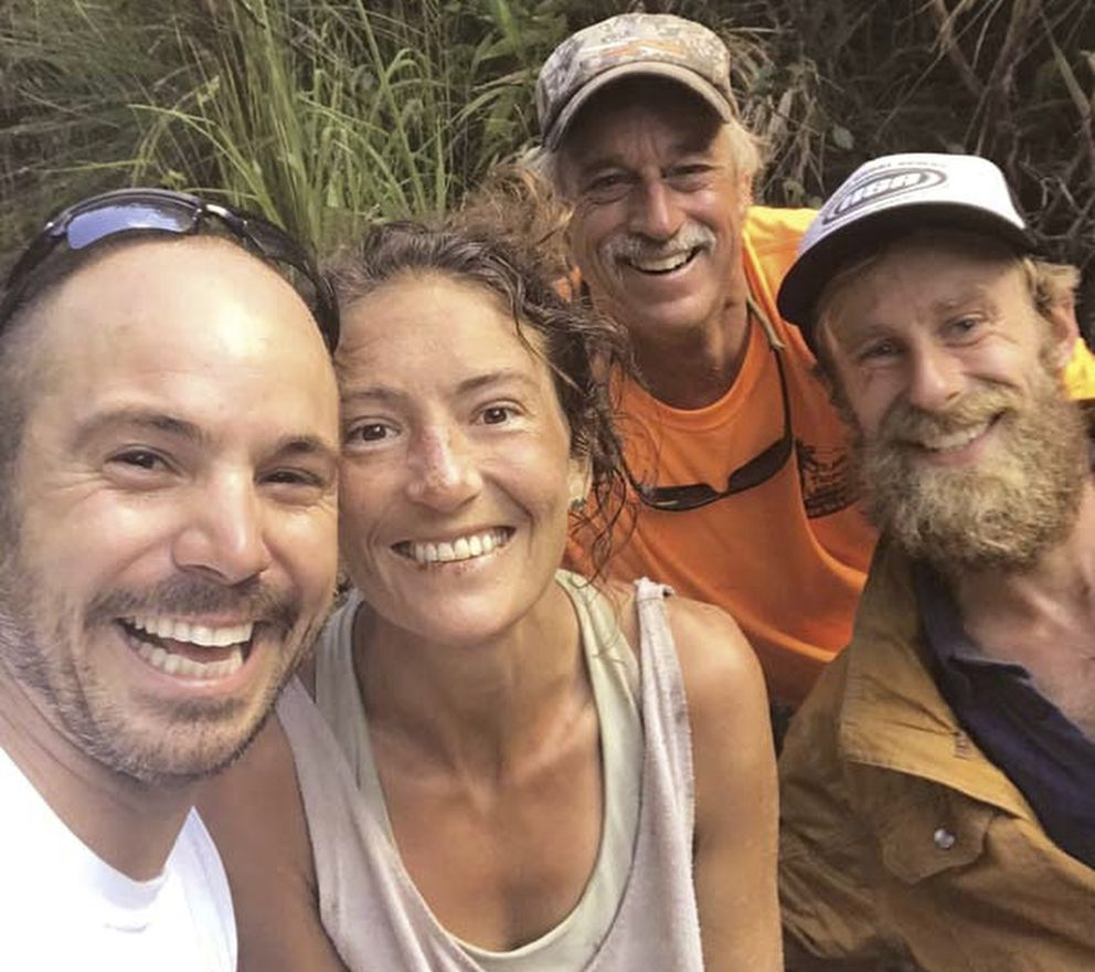 In this Friday, May 24, 2019, photo provided by Troy Jeffrey Helmer, resident Amanda Eller, second from left, poses for a photo after being found by searchers, Javier Cantellops, far left, Helmer and Chris Berquist above the Kailua reservoir in East Maui, Hawaii, on Friday afternoon. The men spotted Eller from a helicopter and went down to retrieve her. She was taken to the hospital and was in good spirits, her family said. Eller had been missing since May 8. (Troy Jeffrey Helmer via AP)