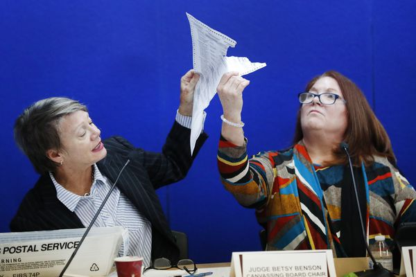 Canvassing Board chair Judge Betsy Benson, left, and board member Judge Deborah Carpenter-Toye, right, show political lawyers one of the ballots that was damaged during the recount that will need to be duplicated and then recounted, at the Broward County Supervisor of Elections office during a recount, Wednesday, Nov. 14, 2018, in Lauderhill, Fla. (AP Photo/Wilfredo Lee)
