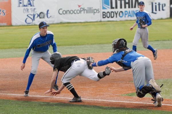 Palmer catcher Skyler Hale tags out South's Josh Costello as Moose third baseman Alasdair McKechnie looks on after Costello was caught in a rundown during a failed squeeze play during Palmer's XX-XX loss to South on Thursday, May 31 in the first round of the ASAA/First National Bank Alaska State High School Baseball Tournament at Mulcahy Stadium. Eight teams are competing in the three-day tournament, including the Moose and Wolverines along with Ketchikan, Juneau, West Valley, Chugiak, North Pole and Colony. (Matt Tunseth/Alaska Star)