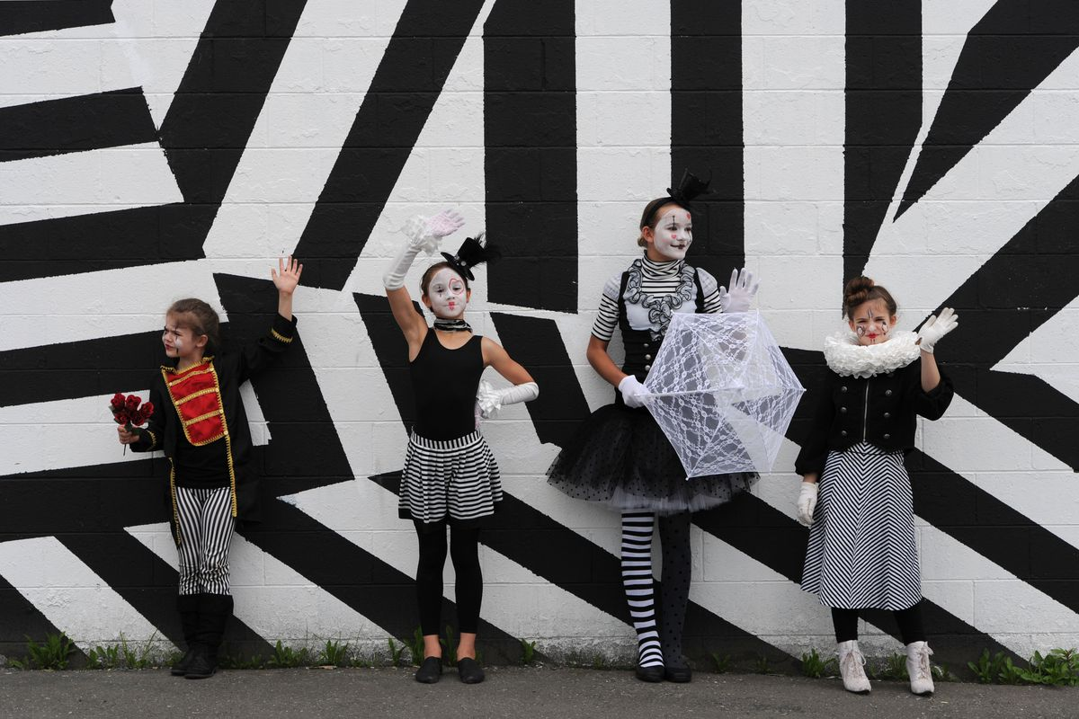 Young mimes Frenchesca Steele, 8; Ivy Erwin, 9; Bright Carr, 12; and Fina Steele, 10, wave to drivers passing through the intersection of Northern Lights Boulevard and Spenard Road on Monday, July 10. Mimes have been spotted at the Spenard Road construction area almost daily. (Bill Roth / Alaska Dispatch News)