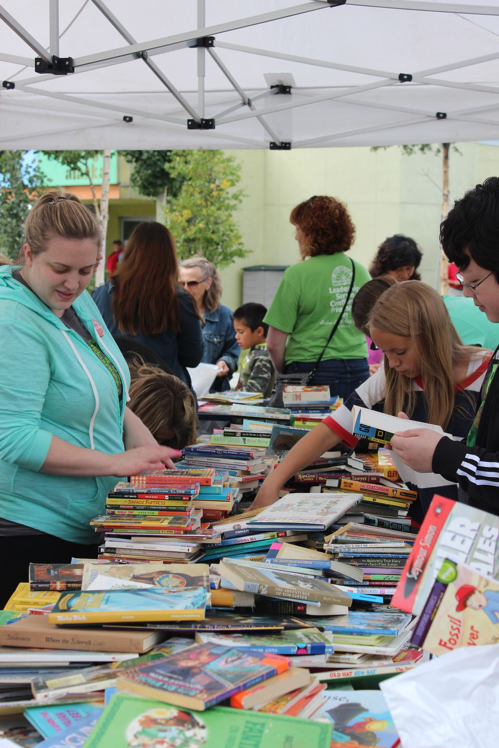 Families choose free books to take home during thread's Book Party in the Park.