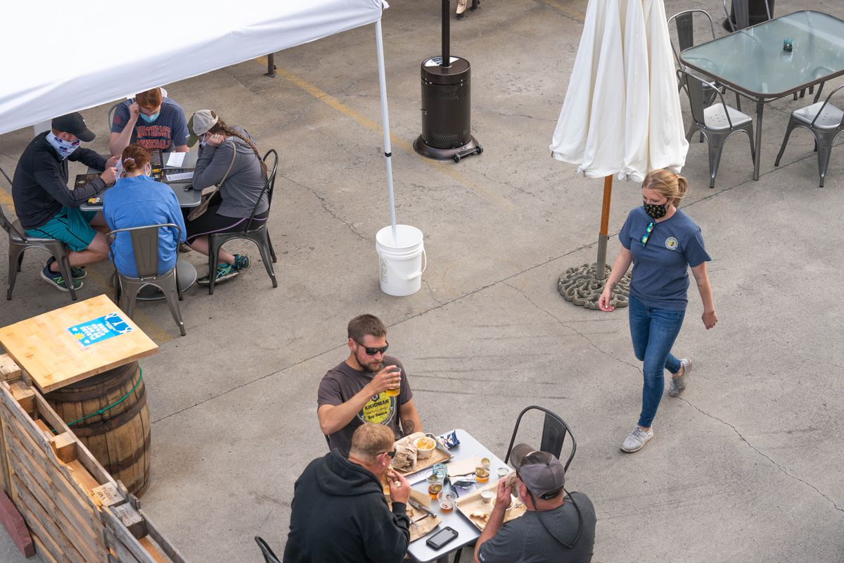 People dine in an outdoor area set up in the parking lot of Midnight Sun Brewing on Thursday, Aug. 13, 2020. (Loren Holmes / ADN)