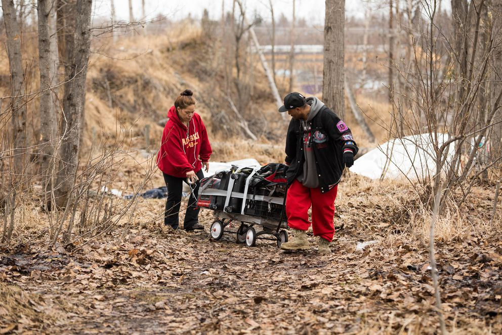 Leah Summers and Carlos Costa move their belongings from their campsite. Summers and Costa said they had been living in the camp for over a year. (Loren Holmes / ADN)