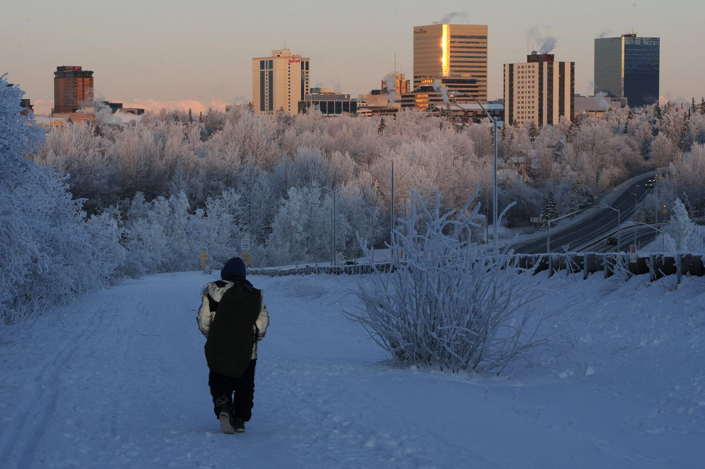 The setting sun casts a warm glow on the Anchorage skyline and frosty trees in the foreground during subzero temperatures on Sunday, Jan. 5, 2020. Shelters for the homeless were at capacity during the cold snap. (Bill Roth / ADN)
