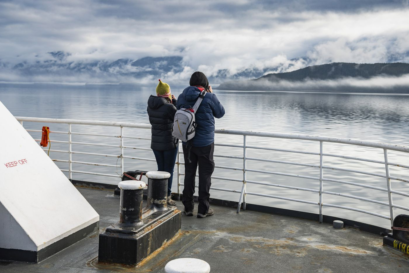 Ferry passengers photograph the foggy shores of Lynn Canal, a 90-mile-long fjord lined with glaciers and snow-capped mountains, in Alaska, April 2018. Following in the footsteps of John Muir — and millions of modern cruise ship passengers — one marine ferry at a time. (Christopher Miller/The New York Times)