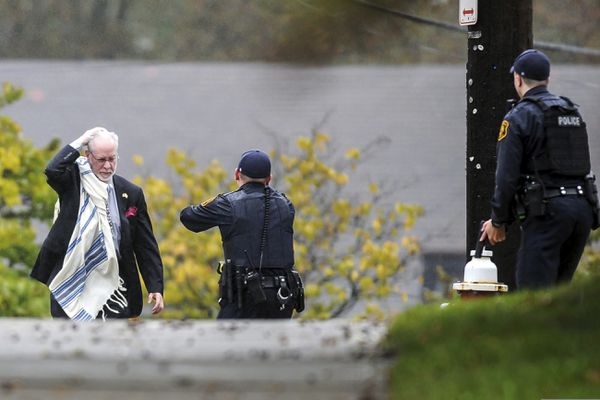 A man holds his head as he's escorted by police out of the Tree of Life Congregation synagogue where multiple people were killed Saturday, Oct. 27, 2018, in the Squirrel Hill section of Pittsburgh. (Alexandra Wimley/Pittsburgh Post-Gazette via AP)