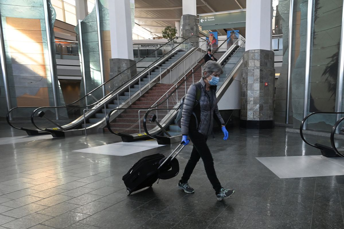 Lita Oppegard walks through the terminal wearing a mask and gloves after arriving at Ted Stevens Anchorage International Airport on Monday, March 23, 2020. (Bill Roth / ADN)