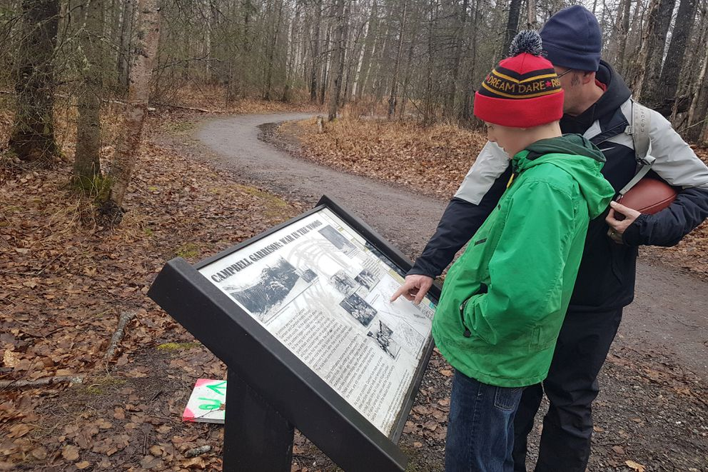 Owen (left) and James Kirkland read an interpretive panel along Viewpoint Trail earlier in the fall. The Campbell Tract's military significance is often missed by users who frequent the area for hiking, biking, or skiing. (Erin Kirkland)