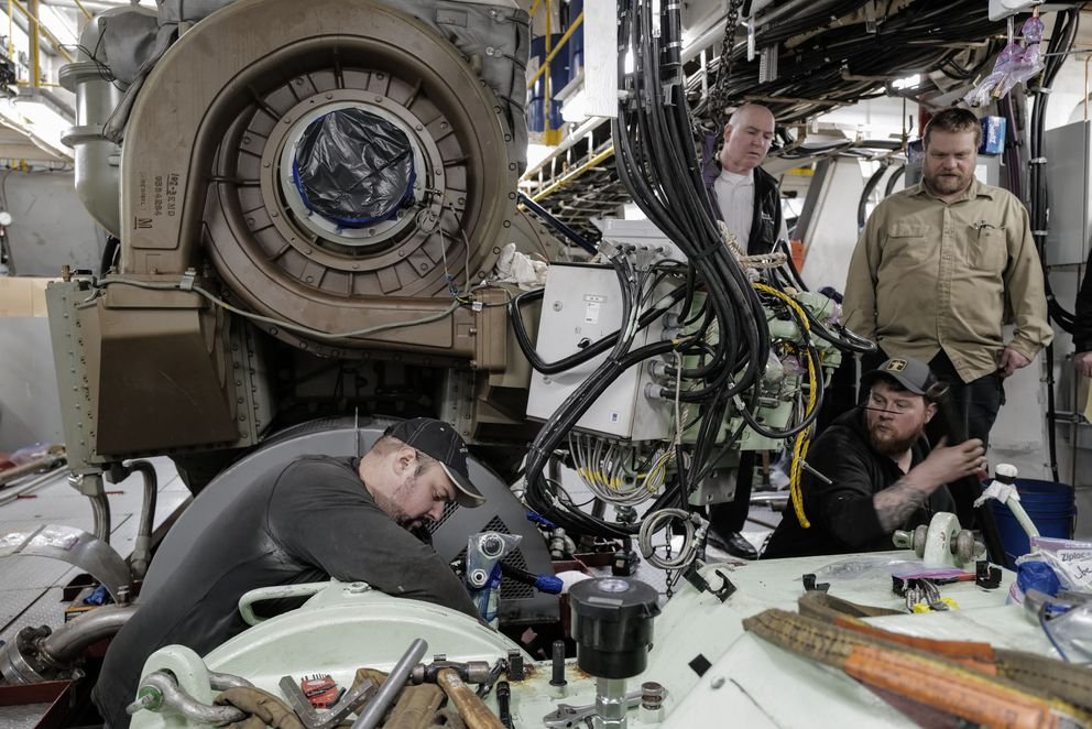 Mechanics Brian Lindgern, left, and Mike Strang, of Vigor Alaska, work on an engine in the Alaska Marine Highway's Matanuska as it is tied up at the Auke Bay Terminal. They are watched by Capt. Dave Turner, back left, and Chief Engineer Eric Downer. (Michael Penn)