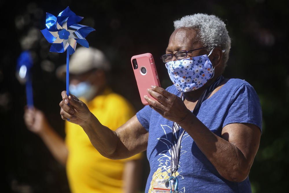 Patricia Brown video chats with her son, who lives in Chicago, while she waves to drivers in a parade at Chugach View and Chugach Manor in Anchorage on July 23, 2020. (Emily Mesner / ADN)